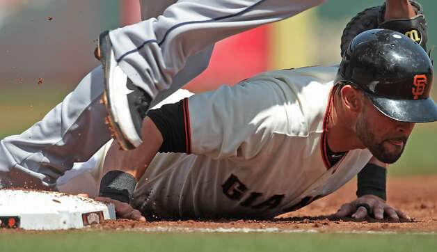 The Giants' Angel Pagan slides safely back into first base on a pick off attempt against the Padres at AT&T Park on Sunday, April 29, 2012, in San Francisco. The ball was overthrown and Pagan went on to score the Giants' first run of their 4-1 victory. Photo: Mathew Sumner, Special To The Chronicle