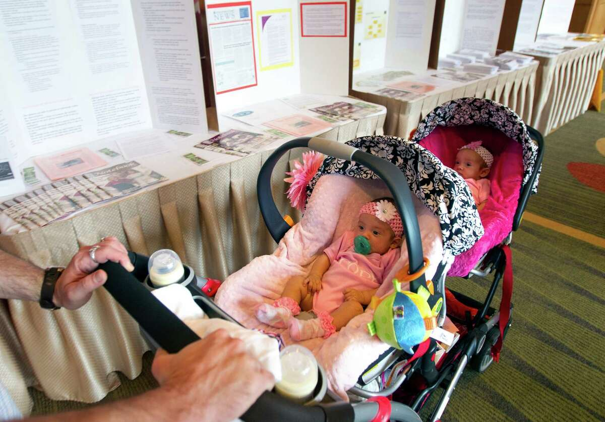 David Phillips pushes his 11-week-old twin daughters Olivia, left, and Juliana amid displays of information during the fourth annual Multiple Birth Awareness Festival on Sunday in Houston.