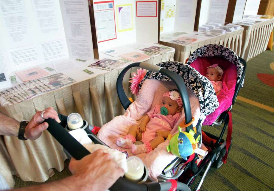 David Phillips pushes his 11-week-old twin daughters Olivia, left, and Juliana amid displays of information during the fourth annual Multiple Birth Awareness Festival on Sunday in Houston. Photo: Cody Duty / © 2011 Houston Chronicle