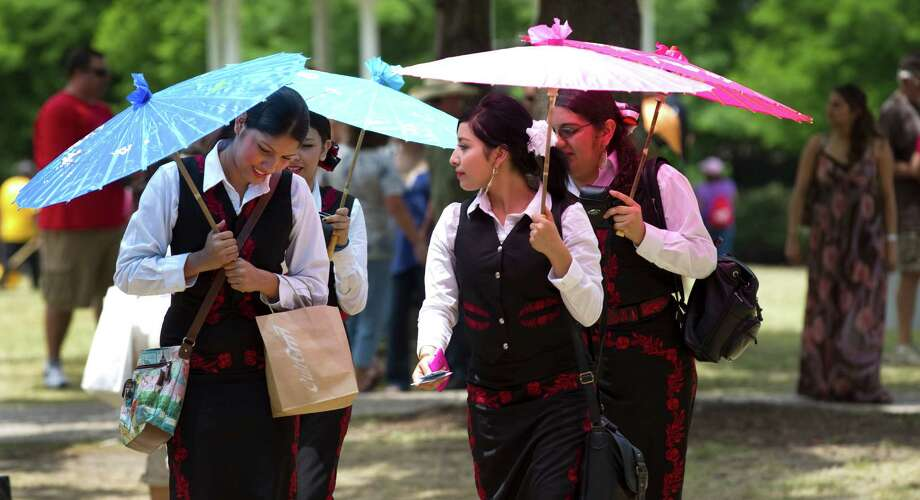 Rebecca Cano, from left, Keyla Castellanos, Sylvia Sandoval and Abigail Aragon, all of Mariachi Los Lobos from Palmview High School wander the festival grounds between performances during the Houston International Festival Sunday, April 29, 2012, in Houston. Photo: Brett Coomer, Houston Chronicle / © 2012 Houston Chronicle