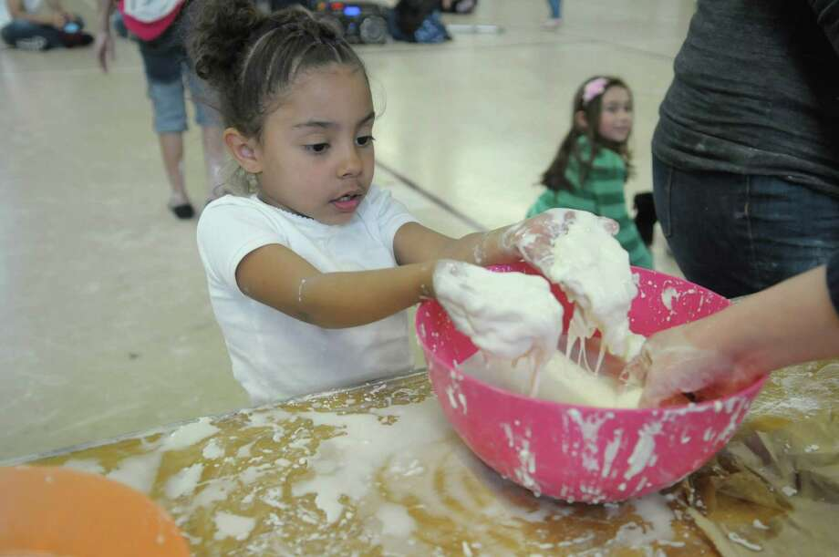 Rhianna Fisher, 5, from Schenectady plays in a bowl of corn starch and water at one of the booths during the annual U-Care Day at the Memorial Fieldhouse on the campus of Union College on Sudnay, April 29, 2012 in Schenectady, NY.   The mixture as set up to show children how the cornstarch and water mixture acts like a solid when under pressure and acts like a liquid at other times.  The event is put on by the college's Kenney Community Center, which is the community outreach department for the college.  Union College student clubs, sports organizations, sororities and fraternities volunteered their time on Sunday to host activities at the event.  Last school year Union College students as a whole gave over 13,000 hours of volunteer service to community groups.  Over 500 children and adults came in to take part in the U-Care Day on Sunday according to organizers.  (Paul Buckowski / Times Union) Photo: Paul Buckowski