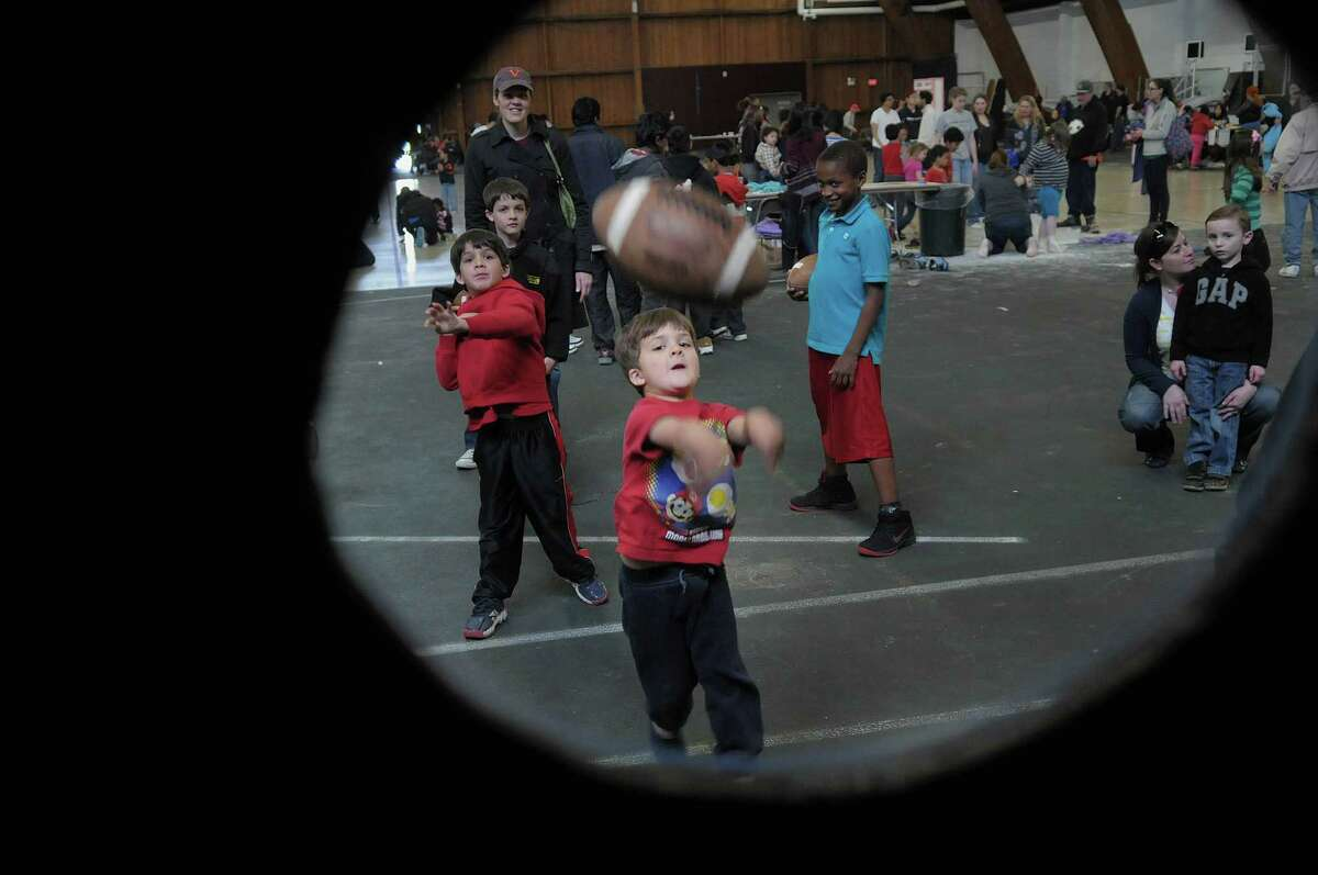 Sami Chowdhrey, 4, from Niskayuna tosses a football towards a hole to try and make it through at one of the games during the annual U-Care Day at the Memorial Fieldhouse on the campus of Union College on Sudnay, April 29, 2012 in Schenectady, NY. The event is put on by the college's Kenney Community Center, which is the community outreach department for the college. Union College student clubs, sports organizations, sororities and fraternities volunteered their time on Sunday to host activities at the event. Last school year Union College students as a whole gave over 13,000 hours of volunteer service to community groups. Over 500 children and adults came in to take part in the U-Care Day on Sunday according to organizers. (Paul Buckowski / Times Union)