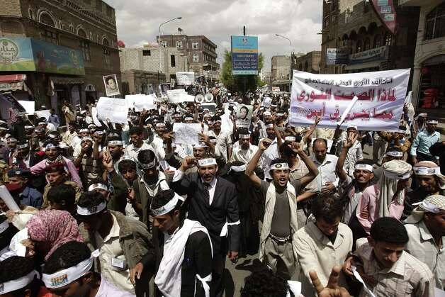 "FILE - In this April 23, 2012, file photo Yemeni members of the Peaceful Revolution Salvation Front chant slogans during a demonstration demanding independence of the judicial system from government control in Sanaa, Yemen. Yemen's al-Qaida of the Arabian Peninsula (AQAP) is becoming a major draw for foreign fighters as it carves out a stronghold in the south of the country, easily defeating Yemeni forces preoccupied battling tribal and political unrest. Arabic on the banner reads, ""Why the revolutionary silence toward what's happening in Abian"", referring to army action against al-Qaida in that area. (AP Photo/Hani Mohammed, File) Photo: Hani Mohammed"