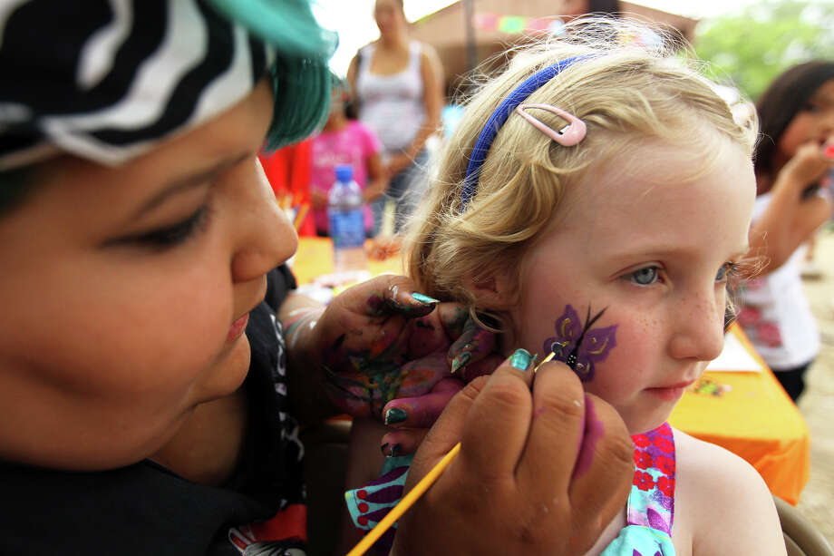 Kassandra Lopez (left) paints a butterfly on the cheek of Chloe Darling, 6, during MissionFest at Mission San José, Sunday, April 29, 2012. Photo: JENNIFER WHITNEY, For The Express-News / special to the Express-News