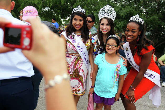 Maribella Cortez, 8, poses for a photo with Miss Fiesta First Princess Miranda Gonzaba (from left), Miss Fiesta Katie Rivera, and Miss Fiesta Second Princess Selina Affram during MissionFest at Mission San José, Sunday, April 29, 2012. Photo: JENNIFER WHITNEY, For The Express-News / special to the Express-News