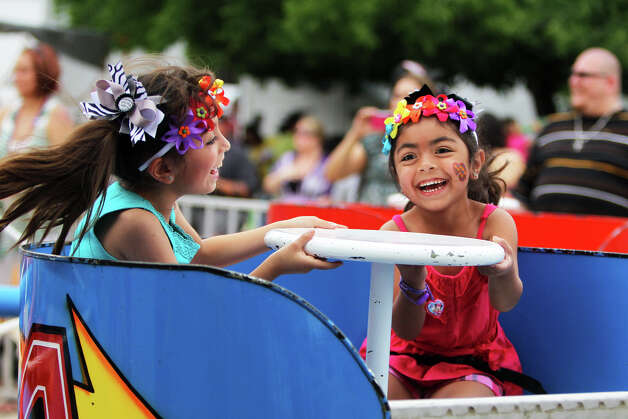 Daniela Garcia, 8 (left), and sister Marina Garcia, 5, spin on a ride at MissionFest at Mission San José. Others there enjoyed the mission itself. Photo: JENNIFER WHITNEY, For The Express-News / special to the Express-News