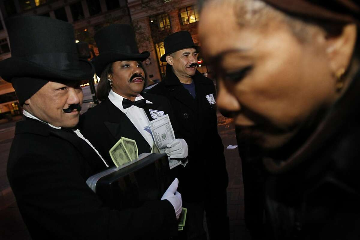 Members of the SEIU local 1021, from left, Norm Ten, Karen Joubert, and David Camham dressed as the Monopoly man and handed out flyers to morning commuters to protest the city's tax breaks for big businesses Thursday morning in San Francisco, Calif., Thursday, April 5, 2012.
