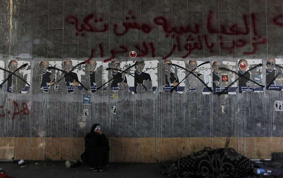 "An Egyptian woman rests under defaced electoral posters of presidential hopeful candidate Ahmed Shafiq at the road leading to the ministry of defense, in Cairo, Egypt Sunday, April 29, 2012. Arabic Reads ""Ahmed Shafiq, Egypt is with everybody and for everybody, Abbasya welcomes the free rebels."" (AP Photo/Nasser Nasser) Photo: Nasser Nasser, Associated Press"