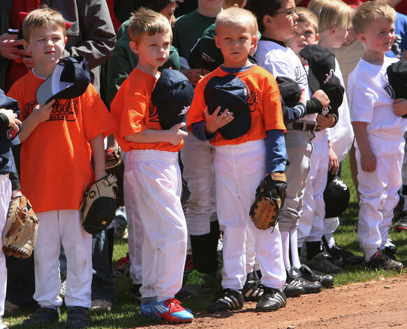 Tigers, orange, from left, Timmy Domicio, Dylan Costanzo, and Garen Killilea, all 6, attend the Fairfield American Little League's opening day ceremonies at Gould Manor Park in Fairfield, Conn. on Sunday, April 29, 2012. Photo: B.K. Angeletti / Connecticut Post