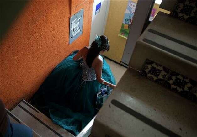 "A fifteen-year-old girl walks down the stairs before the start of a mass ""Quinceanera"" birthday celebration in Mexico City, Saturday, April 28, 2012. The Quinceanera marks the transition from childhood to adulthood and is common in Mexico and other Spanish-speaking countries. (AP Photo/Dieu Nalio Chery) Photo: Chery Dieu Nalio, AP / AP"