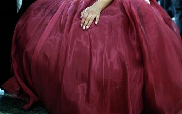 "A girl waits to participate in a mass ""Quinceanera"" birthday celebration in Mexico City, Saturday, April 28, 2012. The Quinceanera marks the transition from childhood to adulthood and is common in Mexico and other Spanish-speaking countries. (AP Photo/Dieu Nalio Chery) Photo: Chery Dieu Nalio, AP / AP"