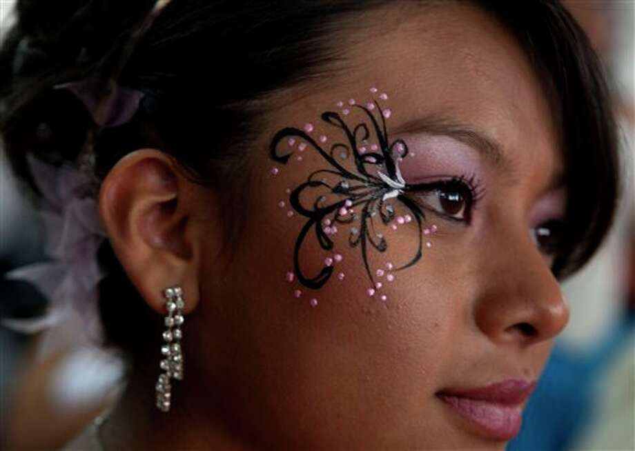 "A 15-year-old girl waits for the start of a mass ""Quinceanera"" birthday celebration in Mexico City, Saturday, April 28, 2012. The Quinceanera marks the transition from childhood to adulthood and is common in Mexico and other Spanish-speaking countries. (AP Photo/Dieu Nalio Chery) Photo: Chery Dieu Nalio, AP / AP"