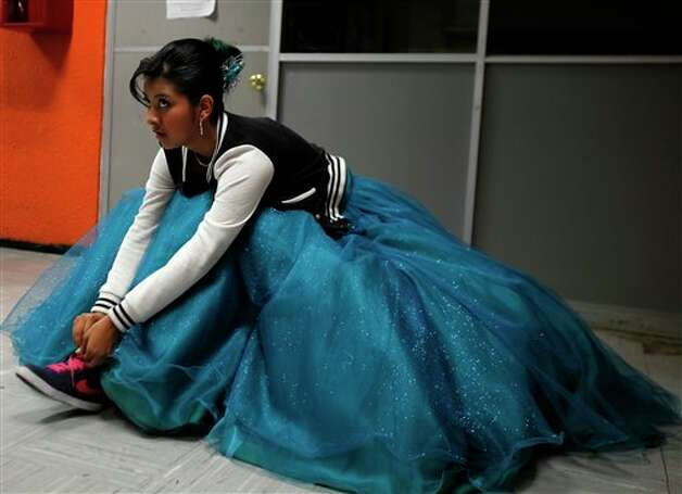 "A 15-year-old girl ties her sneakers as she gets ready for a mass ""Quinceanera"" birthday celebration in Mexico City, Saturday, April 28, 2012. The Quinceanera marks the transition from childhood to adulthood and is common in Mexico and other Spanish-speaking countries. (AP Photo/Dieu Nalio Chery) Photo: Dieu Nalio Chery, AP / AP"