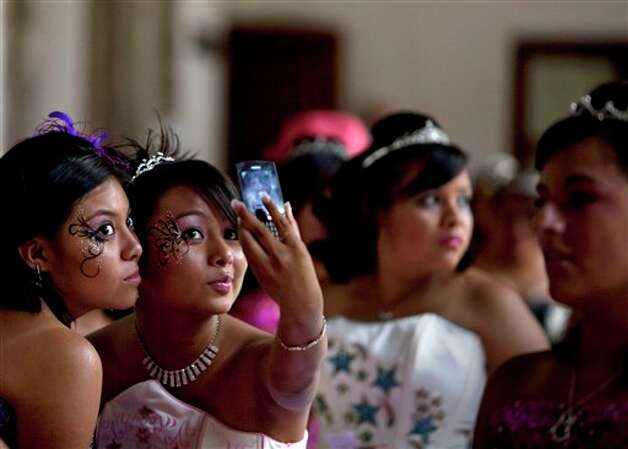 "Fifteen-year-old girls take pictures of themselves during a mass ""Quinceanera"" birthday celebration in Mexico City, Saturday, April 28, 2012. The Quinceanera marks the transition from childhood to adulthood and is common in Mexico and other Spanish-speaking countries. (AP Photo/Dieu Nalio Chery) Photo: Dieu Nalio Chery, AP / AP"