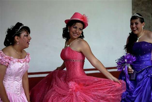 "Cecilia, center, 15-year-old girl plays with her dresse before a mass ""Quinceanera"" birthday celebration in Mexico City, Saturday, April 28, 2012. The Quinceanera marks the transition from childhood to adulthood and is common in Mexico and other Spanish-speaking countries. (AP Photo/Dieu Nalio Chery) Photo: Dieu Nalio Chery, AP / AP"
