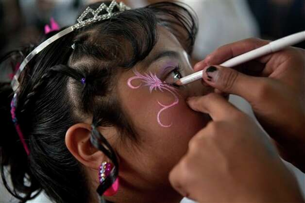 "A 15-year-old girl gets her make-up done before a mass ""Quinceanera"" birthday celebration in Mexico City, Saturday, April 28, 2012. The Quinceanera marks the transition from childhood to adulthood and is common in Mexico and other Spanish-speaking countries. (AP Photo/Dieu Nalio Chery) Photo: Dieu Nalio Chery, AP / AP"
