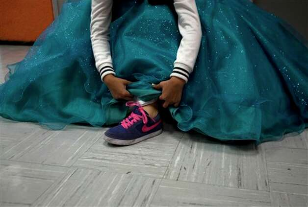 "A 15-year-old girl gets ready for a mass ""Quinceanera"" birthday celebration in Mexico City, Saturday, April 28, 2012. The Quinceanera marks the transition from childhood to adulthood and is common in Mexico and other Spanish-speaking countries. (AP Photo/Dieu Nalio Chery) Photo: Dieu Nalio Chery, AP / AP"