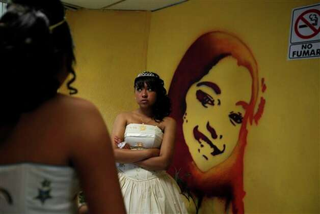 "A girl waits before a mass ""Quinceanera"" birthday celebration in Mexico City, Saturday, April 28, 2012. The Quinceanera marks the transition from childhood to adulthood and is common in Mexico and other Spanish-speaking countries. (AP Photo/Dieu Nalio Chery) Photo: Chery Dieu Nalio, AP / AP"
