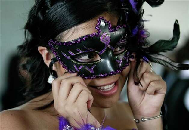 "A girl wears a mask during a mass ""Quinceanera"" birthday celebration in Mexico City, Saturday, April 28, 2012. The Quinceanera marks the transition from childhood to adulthood and is common in Mexico and other Spanish-speaking countries. (AP Photo/Dieu Nalio Chery) Photo: Chery Dieu Nalio, AP / AP"