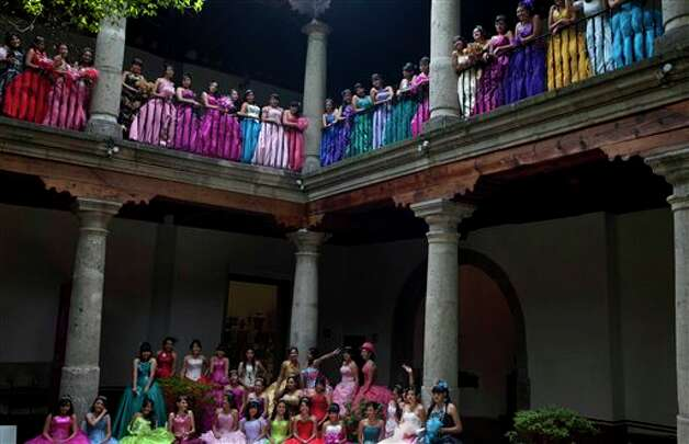 "Fifteen-year-old girls pose for a group picture at the Franz Mayer museum before a mass ""Quinceanera"" birthday celebration in Mexico City, Saturday, April 28, 2012. The Quinceanera marks the transition from childhood to adulthood and is common in Mexico and other Spanish-speaking countries. (AP Photo/Dieu Nalio Chery) Photo: Dieu Nalio Chery, AP / AP"