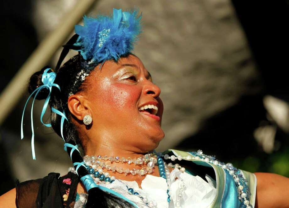 Jennifer Jones dances with the Treme Brass band at a sunrise concert marking International Jazz Day in New Orleans, Monday, April 30, 2012. The performance, at Congo Square near the French Quarter, is one of two in the United States that day; the other is in the evening in New York. Thousands of people across the globe are expected to participate in International Jazz Day, including events in Belgium, France, Brazil, Algeria and Russia. (AP Photo/Gerald Herbert) Photo: Gerald Herbert, Associated Press / AP