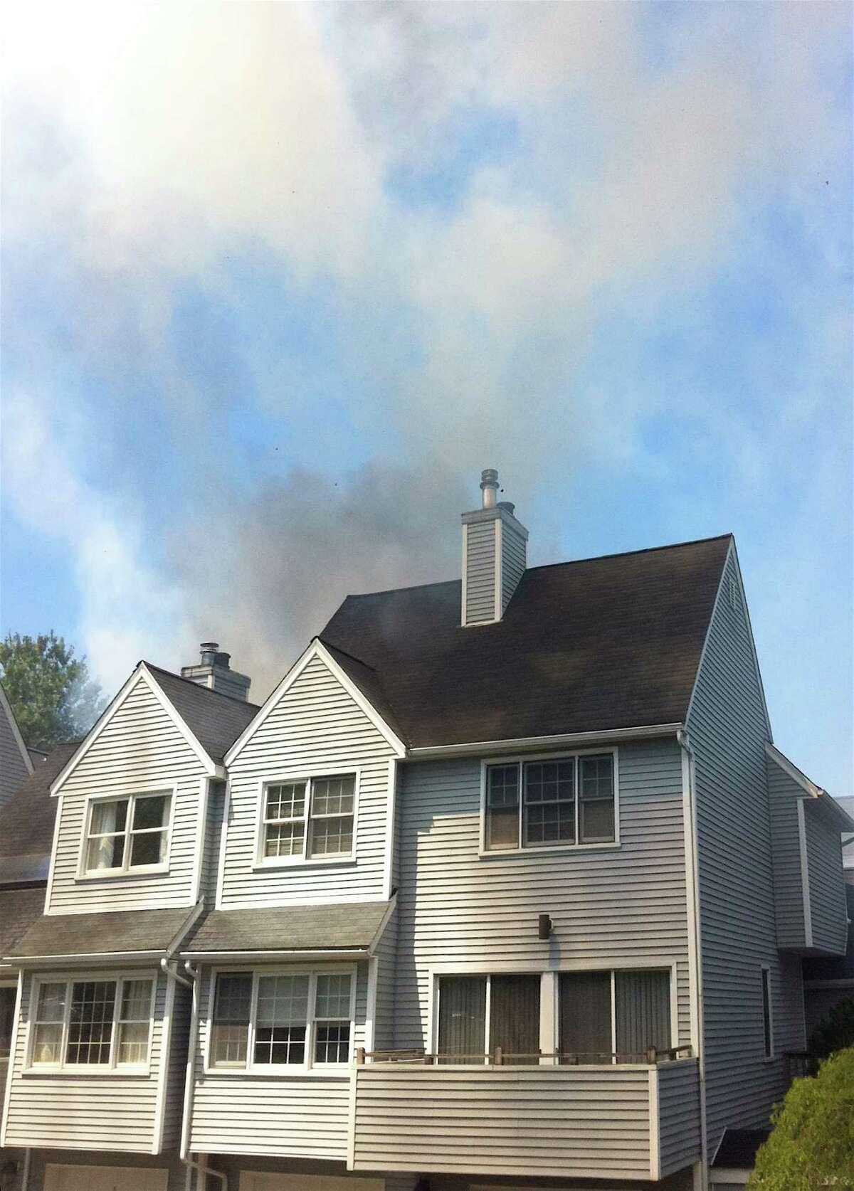 Smoke billows at a condo fire on Wilton Crest Road in Wilton, Conn., Sunday, April 29, 2012.