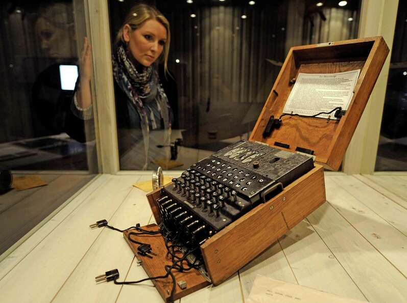 A woman watches an original German ENIGMA cipher machine from World War II at the new spy museum in
