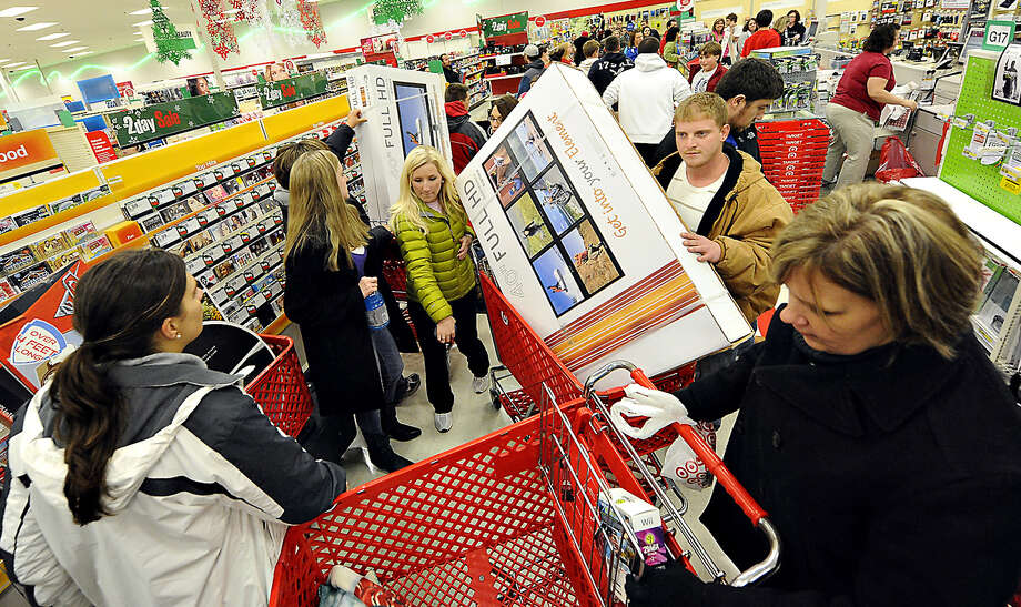 In this Nov. 25, 2011 file photo, shoppers scramble for door buster deals at Target, in Bowling Green, Ky. Americans increased their spending more slowly in March 2012, suggesting some could be worried about the economy. (AP Photo/Daily News) Photo: Associated Press / AP2011