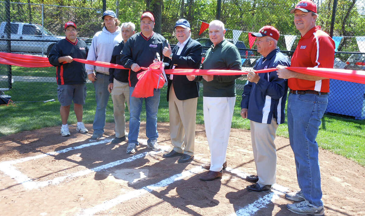 Fairfield American Little League officials, joined by First Selectman Michael Tetreau and other town officials, prepare to cut ribbon at Sunday's dedication of the league's new fields in Gould Manor Park.