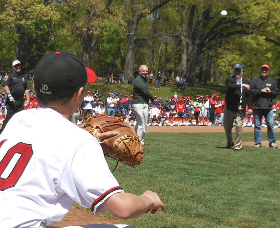 First Selectman Michael Tetreau throws out the first pitch at the dedication Sunday for new baseball fields of the Fairfield American Little League in Gould Manor Park. Photo: Mike Lauterborn / Fairfield Citizen contributed