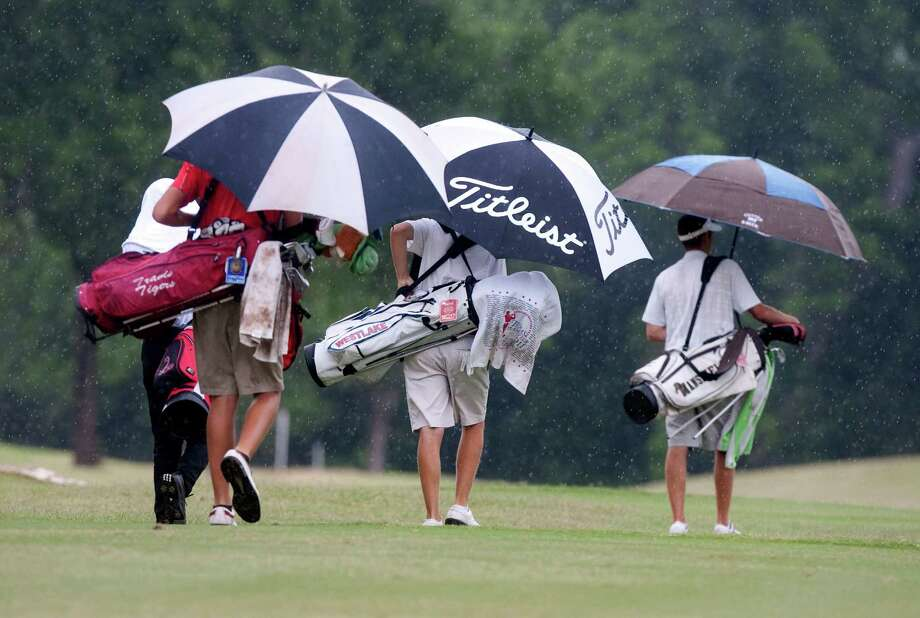 Golfers walk hole one during a brief shower during the first round of the Class 5A state golf tournament at Onion Creek Golf Course on Monday, April 30, 2012 in Austin. Photo: J. Patric Schneider, For The Chronicle / Houston Chronicle