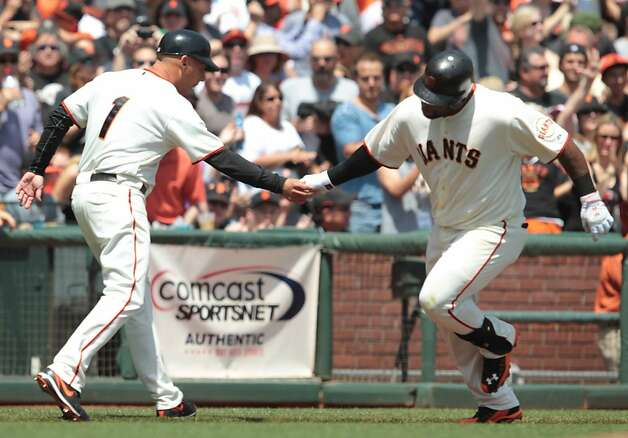 The Giants' Pablo Sandoval is congratulated by third base coach Tim Flannery after his solo home run in the first inning against the Padres at AT&T Park on Sunday, April 29, 2012, in San Francisco. The Giants' won 4-1. Photo: Mathew Sumner, Special To The Chronicle