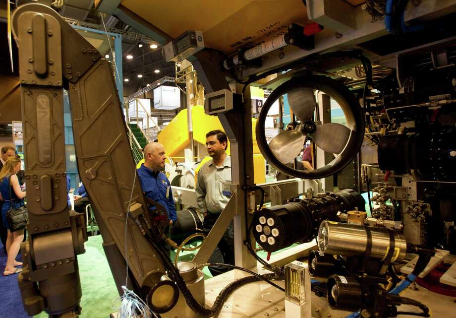 Ian Roberts, lof Saipem America, left, and Venkatachala Minikanti, of Down Chemical, talk near a submersible robot during the 2012 Offshore Technology Conference Monday, April 30, 2012, in Houston. Photo: Brett Coomer, Houston Chronicle / © 2012 Houston Chronicle