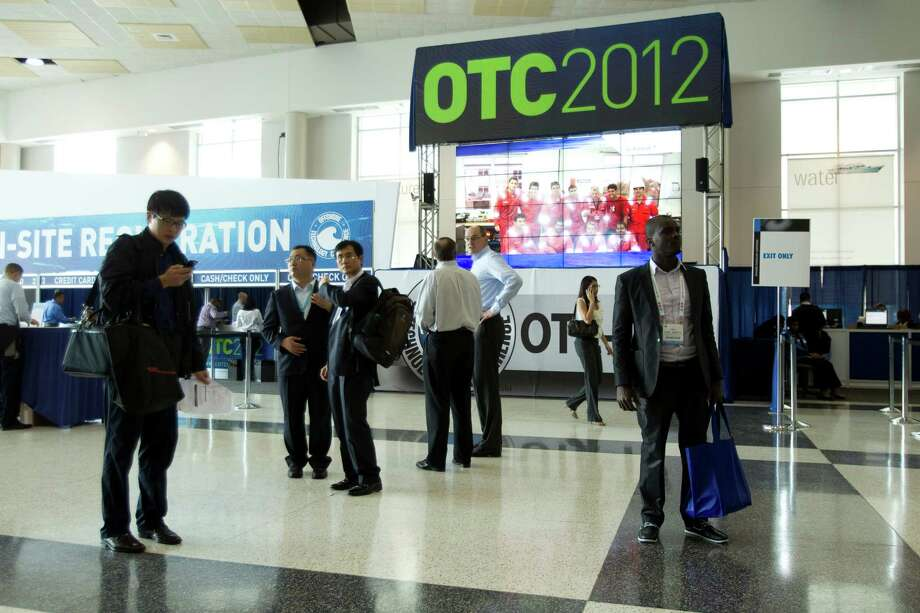 Attendees to the 2012 Offshore Technology Conference walk past the registration center Monday, April 30, 2012, in Houston. Photo: Brett Coomer, Houston Chronicle / © 2012 Houston Chronicle