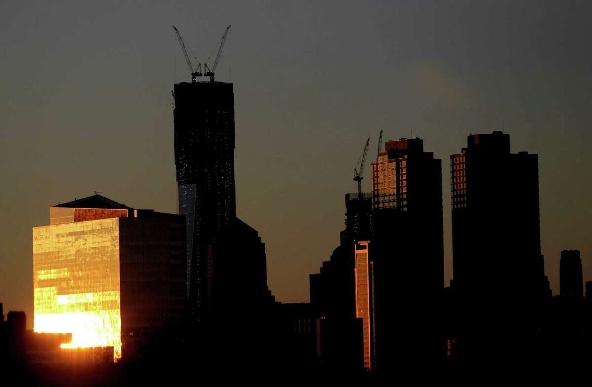 The sun reflects on a building as it rises Monday, including One World Trade Center, center left, in New York as seen from Jersey City, N.J. One World Trade Center, the giant monolith being built to replace the twin towers destroyed in the Sept. 11 attacks, became New York City's tallest skyscraper on Monday.
