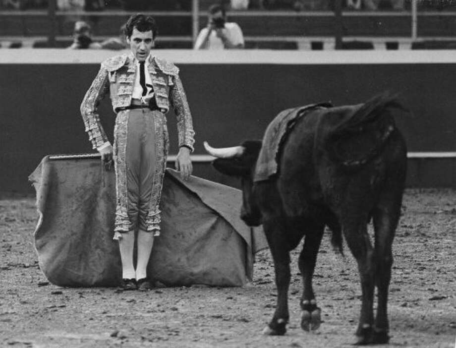 Matador Jaime Bravo tries to stare down el toro who paws the dirt and twitches his tail, February 1966.  (David Nance / Chronicle file)