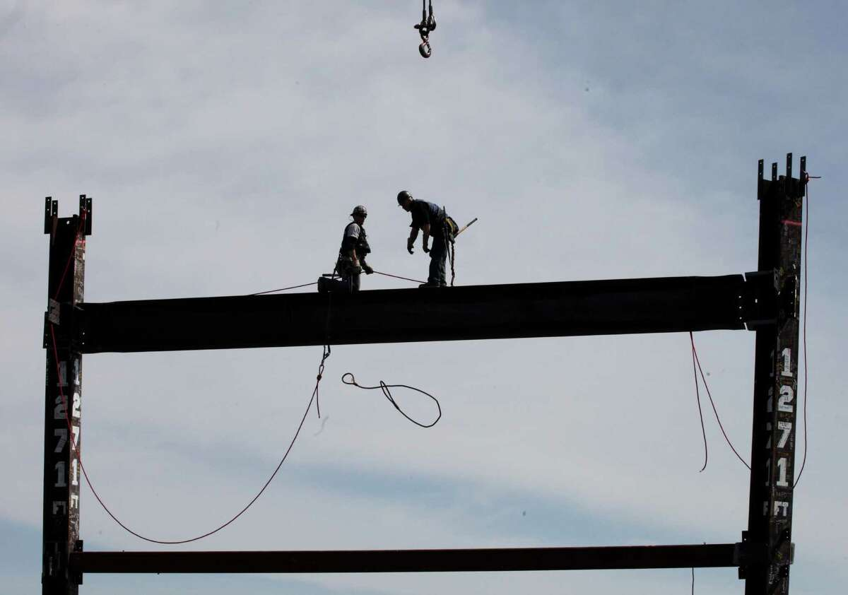 Ironworkers Jim Brady, left, and Billy Geoghan release a steel cable after connecting a steel beam between two columns at the top of One World Trade Center to make it New York City's tallest skyscraper, Monday,in New York. One World Trade Center is being built to replace the twin towers destroyed in the Sept. 11 attacks. It reached just over 1,250 feet on Monday. That's just taller than the observation deck on the Empire State Building.