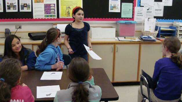 Jessica Richards, 11, a fifth-grader at North Stratfield School, stands in front of the classroom of fifth-grade teacher Jan Ramstedt to act as a student teacher for the day. Jessica's lesson built on a poetry unit that Ramstedt was teaching. She and three other students got the temporary teaching assignment through an auction held every other year by the PTA to raise funding for student activities at the school. Photo: Meg Barone / Fairfield Citizen freelance