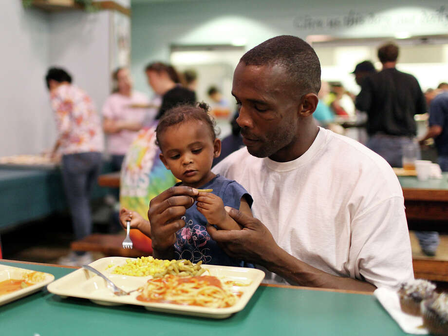 Ricardo Lawson feeds his daughter Unique Galindo after a worship service Thursday March 29, 2012 at Church Under the Bridge. Lawson is homless but his daughter lives with her mother who is not homeless. Photo: EDWARD A. ORNELAS, SAN ANTONIO EXPRESS-NEWS / © SAN ANTONIO EXPRESS-NEWS (NFS)