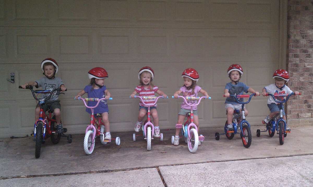 Mark Phillips and his siblings, quintuplets Kate, Becca, Ali, David, and John, on their bicycles.