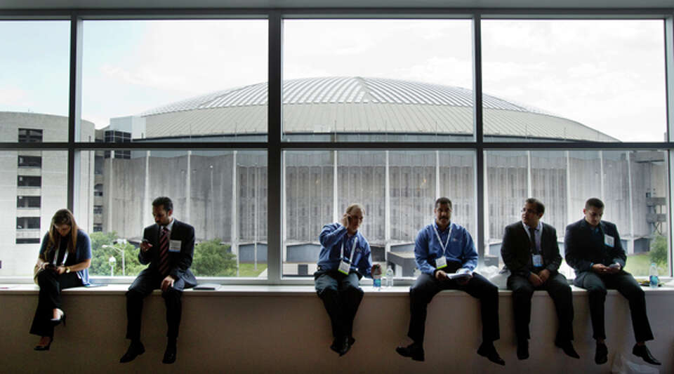 Attendees to the 2012 Offshore Technology Conference sit on a window ledge, with the Astrodome shown