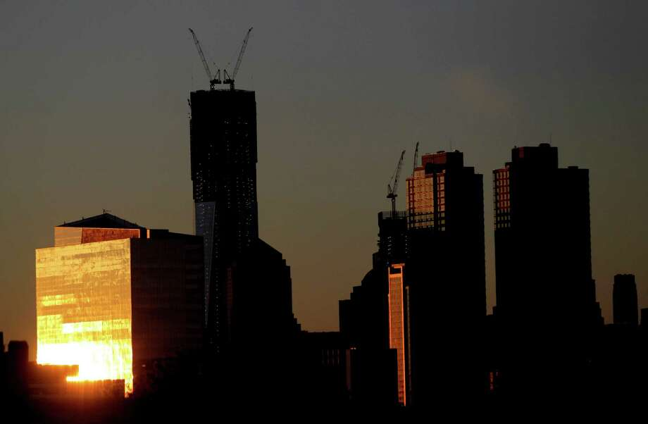 The sun reflects on a building as it rises Monday April 30, 2012, including One World Trade Center, center left, in New YOrk as seen from Jersey City, N.J. One World Trade Center, the giant monolith being built to replace the twin towers destroyed in the Sept. 11 attacks, will lay claim to the title of New York City's tallest skyscraper on Monday.   (AP Photo/Julio Cortez) Photo: Julio Cortez