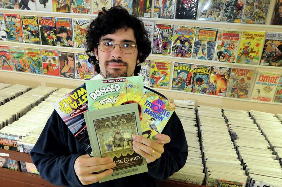 Shop owner Dan Cruson holds free offerings on Thursday, April 26, 2012, at The Goblin's Cavern in Lansingburgh, N.Y. Cruson ordered 500 comic books for Free Comic Book Day, which is May 5. (Cindy Schultz / Times Union) Photo: Cindy Schultz / 00017393A
