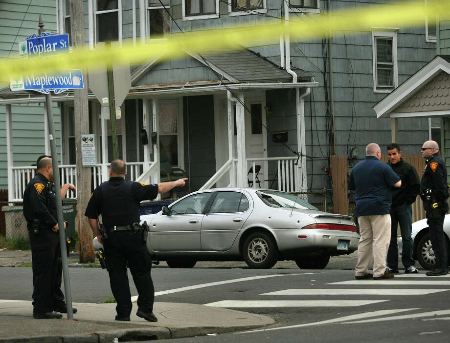 Bridgeport police investigate a shooting scene at the intersection of Maplewood Avenue and Poplar Street outside Bryant School on Bridgeport's West Side on Monday, April 30, 2012. A three-year-old girl was wounded in the crossfire. The car at center has several visible bullet holes and a shattered rear window. Photo: Brian A. Pounds / Connecticut Post
