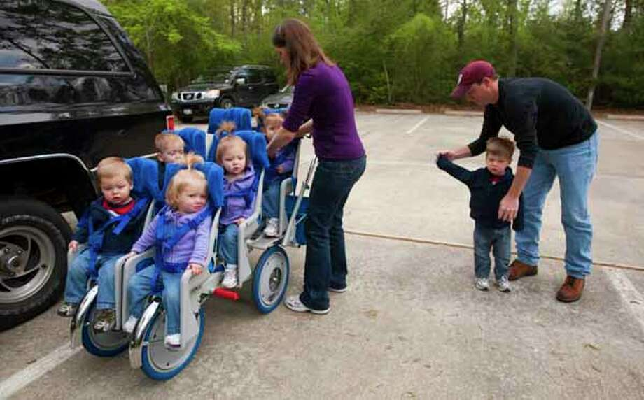 Kelly and Bill Phillips load their children onto their six-seat stroller as they get out of the car for a Mothers of Multiples event at Forestgate Park Saturday, March 27, 2010, in The Woodlands. Kelly is working with quintuplets, from front left: David, Becca, second row from left, John and Kate, with Ali in the back row. Bill is helping older brother Mark, 2, with his jacket. Photo: Brett Coomer, . / Houston Chronicle