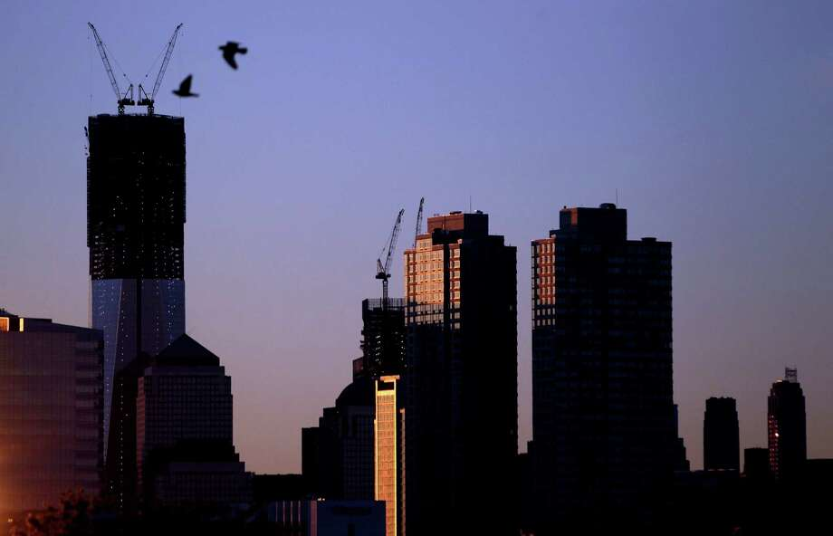Viewed from Jersey City, N.J., two birds fly by as the sun rises over buildingsin New York, including One World Trade Center, tallest building at left, Monday, April 30, 2012. One World Trade Center, the giant monolith being built to replace the twin towers destroyed in the Sept. 11 attacks, will lay claim to the title of New York City's tallest skyscraper on Monday.  (AP Photo/Julio Cortez) Photo: Julio Cortez, Associated Press / AP