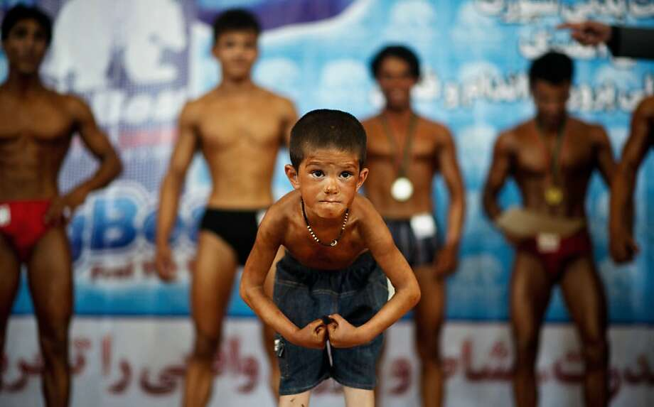 Do NOT kick sand on him at the beach or you'll be sorry: A young boy flexes during a bodybuilding competition in Kabul. Photo: Johannes Eisele, AFP/Getty Images