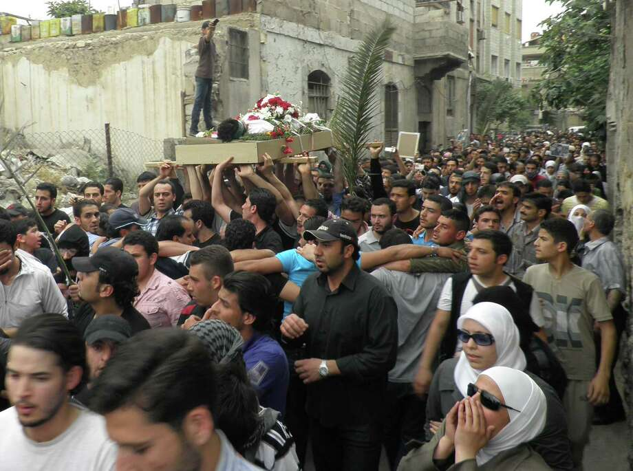 Anti-Syrian regime mourners shout slogans and carry the body of activist Nour al-Zahraa, 23, who was shot by Syrian security forces on Sunday, during his funeral procession, in the Kfar Suseh area, in Damascus, Syria, on Monday, April 30, 2012. (AP Photo) Photo: Anonymous / AP