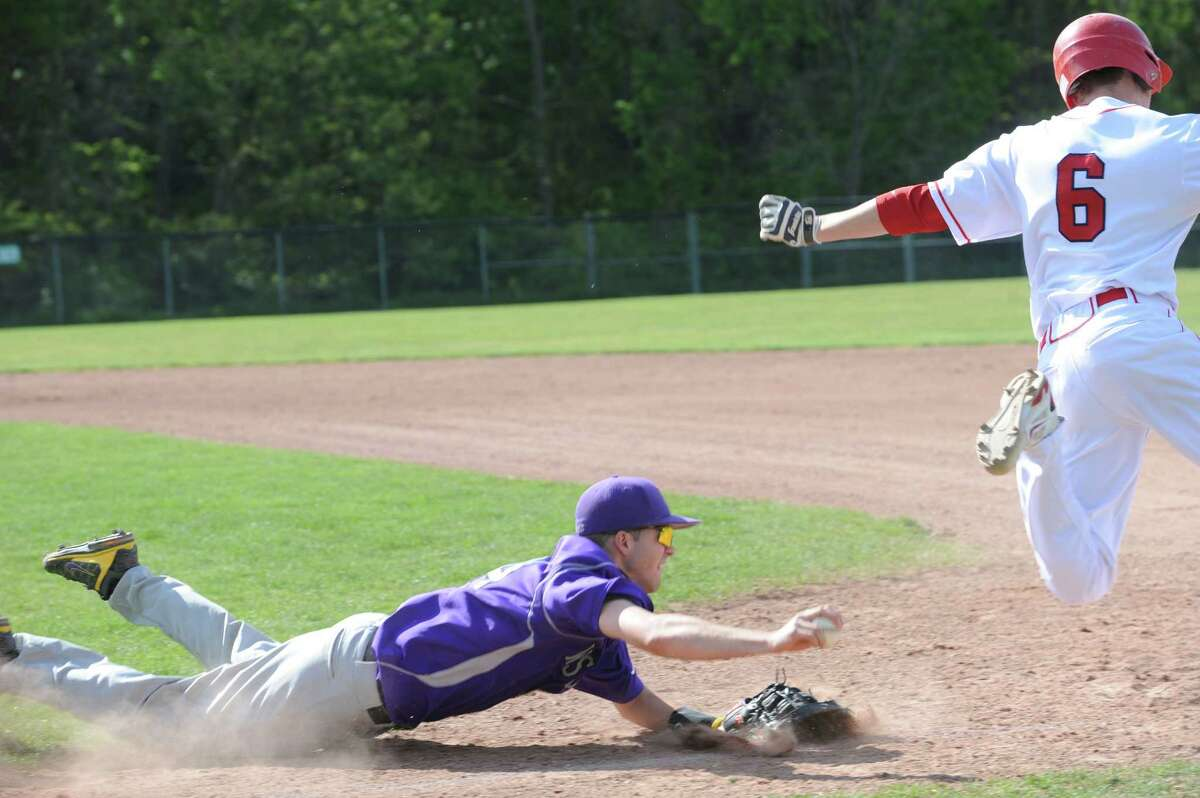Westhill High School's # 24, Andrew Oakes slides while Greenwich High School's # 6, Vincent Ferraro made it to first base at baseball hosted by Greenwich Monday, April 30, 2012. Greenwich High School won 5 to 1 against Westhill High School.