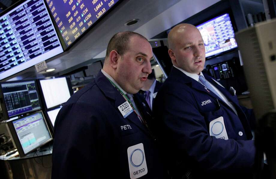 Specialists Peter Giacchi, left, and John Parisi confer on the floor of the New York Stock Exchange Wednesday, April 25, 2012.  U.S. stocks were headed for a neutral opening, with Dow Jones industrial futures nearly unchanged.  (AP Photo/Richard Drew) Photo: Richard Drew